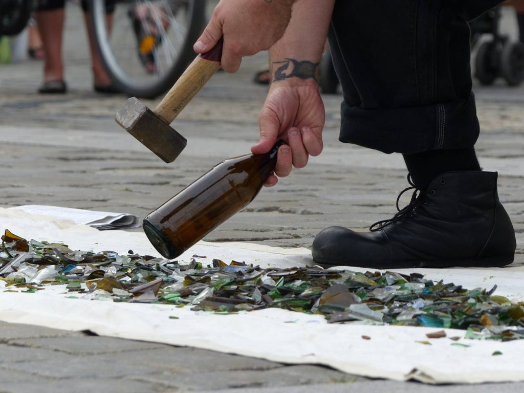 A busker breaking glass during a street show
